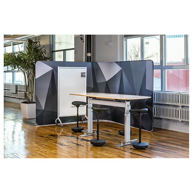 Work area with adjustable standing height table with ergonomic stools in office space in older building